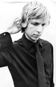 Photo of Beck looking down and scratching the back of his head.