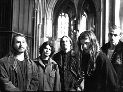 A picture of the members of Blind Melon wearing coats and standing together in a cathedral.