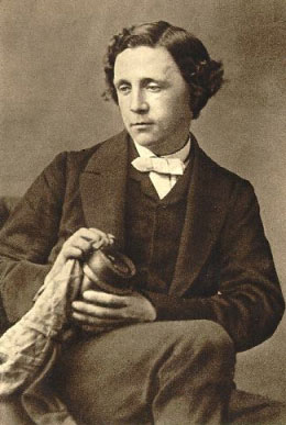 A portrait of Lewis Carroll seated, wearing a suit, holding an object, and looking down and to the left.