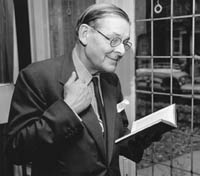 Photo of T. S. Eliot smiling and reading from a book with his other hand grasping the fold of his suit.