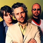 An image of band members from The Flaming Lips standing in front of a yellow background doing nothing in particular.