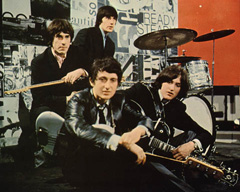 A picture of the members of the Kinks resting on a stage around a drumset with their instruments.
