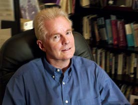 A photograph of David Kirby smiling faintly while seated in an office chair turned slightly away (This is a link to his website).