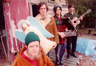Picture of band members from Neutral Milk Hotel standing around a rundown shack holding various items.