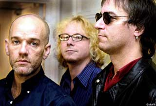 Photograph of the R.E.M. band members standing beside each other looking in different directions.