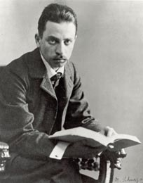 Image of Rainier Maria Rilke looking ahead while seated in an old chair with a book in his hands.