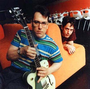 Photo of the Johns from They Might Be Giants on a big orange chair with Flansburgh in front and Linnell in back (This is a link to their website).