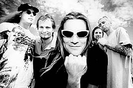 A photograph of the Ugly Kid Joe band members standing together with the sky and clouds behind them.