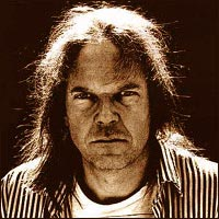 A sepia image of Neil Young in a striped shirt staring ahead meanly with light from behind him reflecting off of his hair.